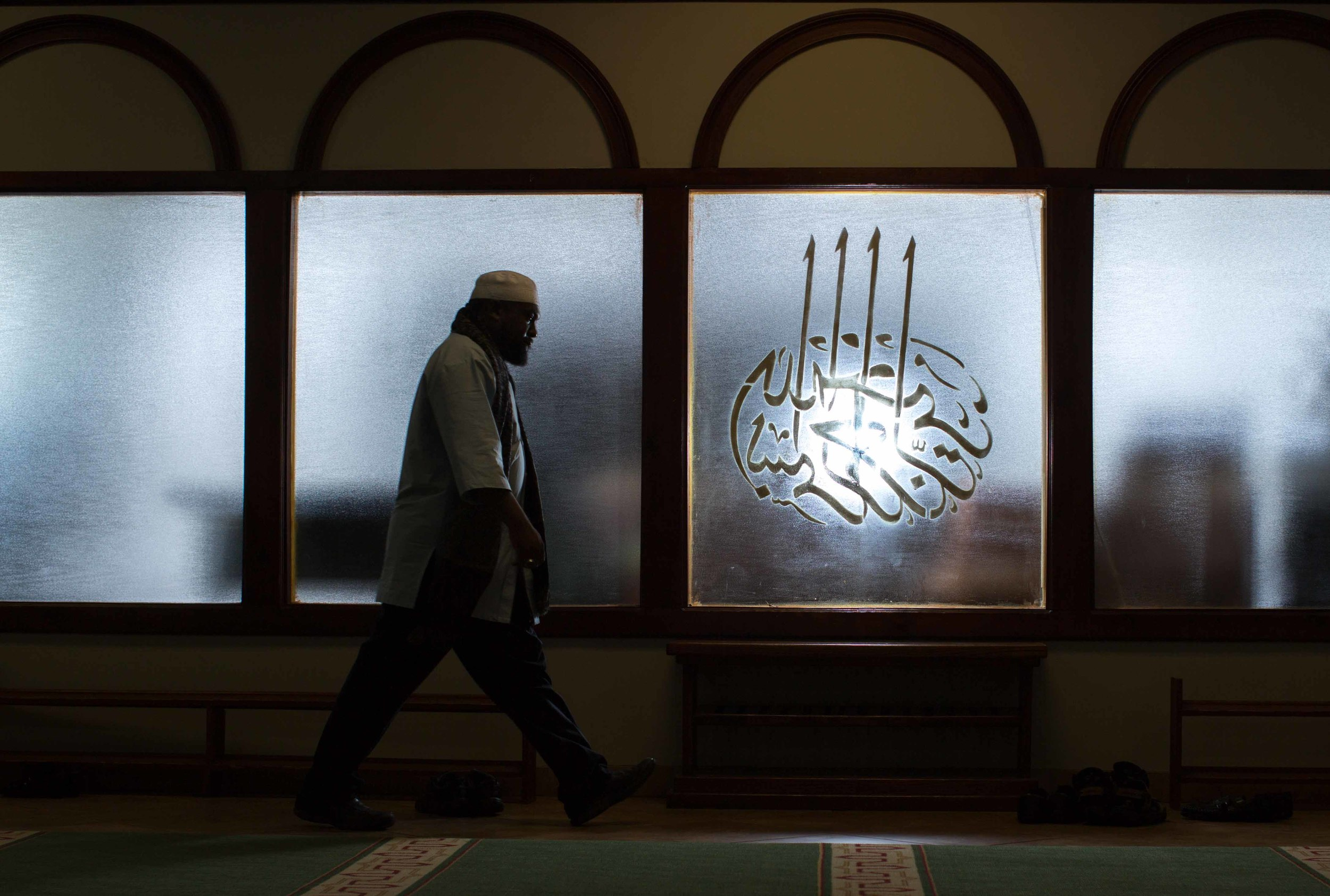 In this Sunday, Aug. 30, 2015 photo, Imam Suleimaan Hamed, the leader of the Atlanta Masjid of Al Islam mosque, walks through the mosque, in Atlanta. Members of the mosque gathered to celebrate a group of pilgrims who will make the annual hajj pilgrimage to the holy city of Mecca. (AP Photo/Branden Camp)