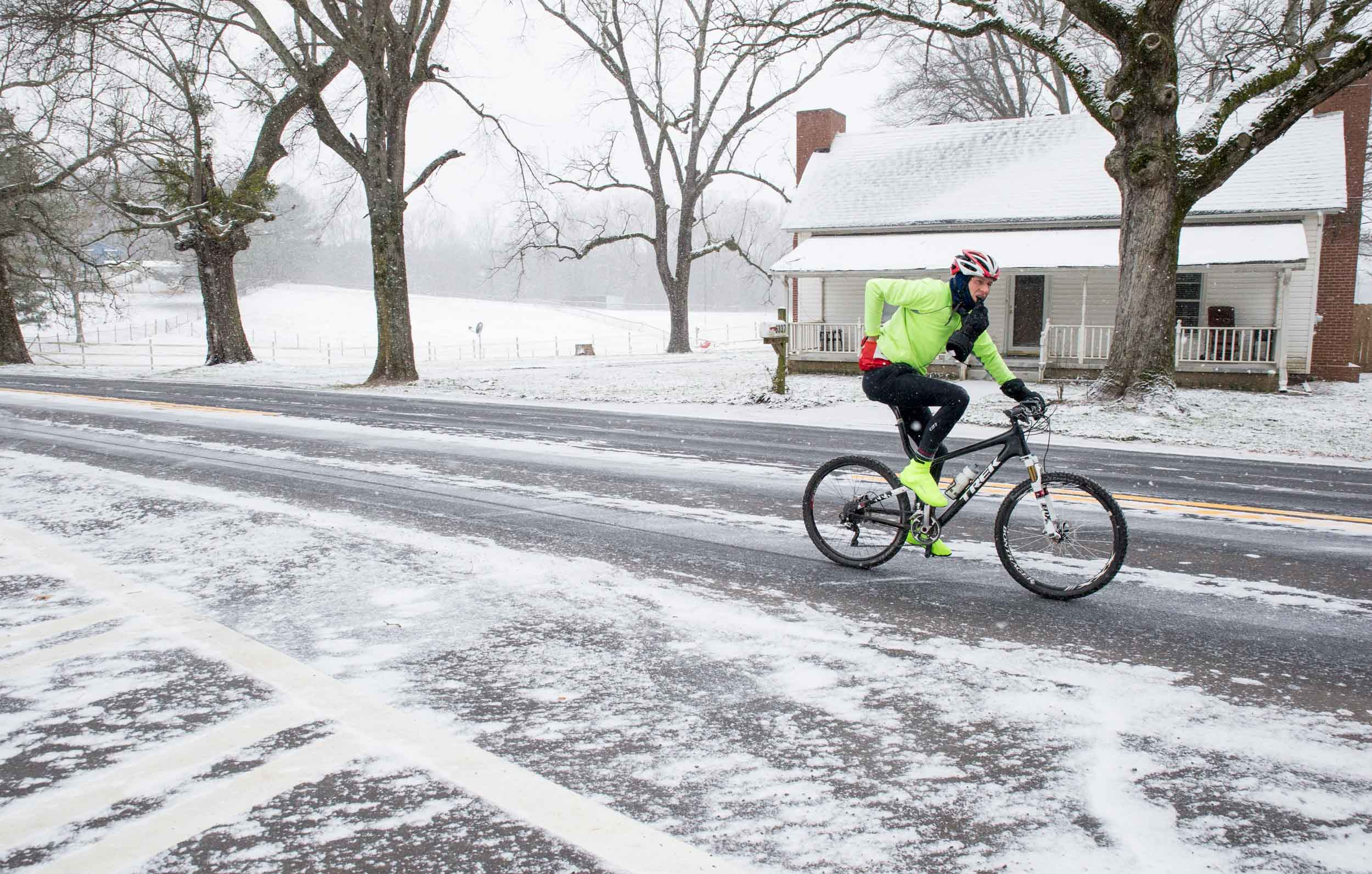A cyclist rides on an ice covered street during a light snow fall, Saturday, Jan. 23, 2016, in Woodstock, Ga.