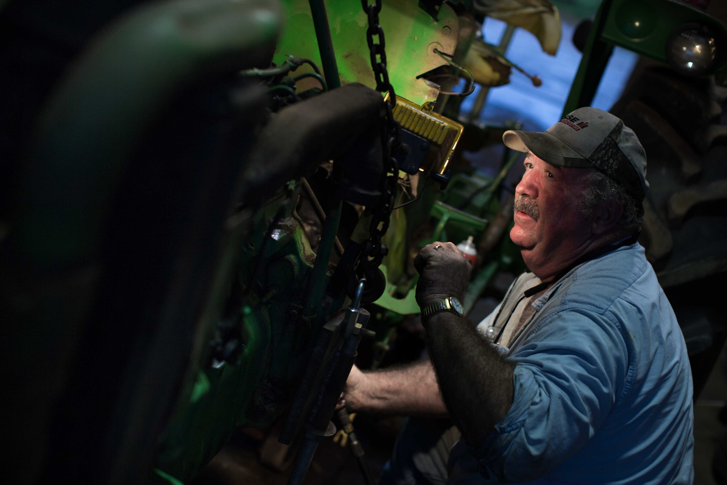 Farmer Phil Sanders works on his John Deere tractor at Buffalo Creek Straw and Seed Farm, Wednesday, Feb. 3, 2016, in Stephens, Ga.With over 42,000 farmers working in the Georgia agriculture industry, farming contributes over $73 Billion to Georgia's economy each year. Forecasters say profits are expected be down as well as exports nationwide due to a fragile world economy. Photo by Branden Camp