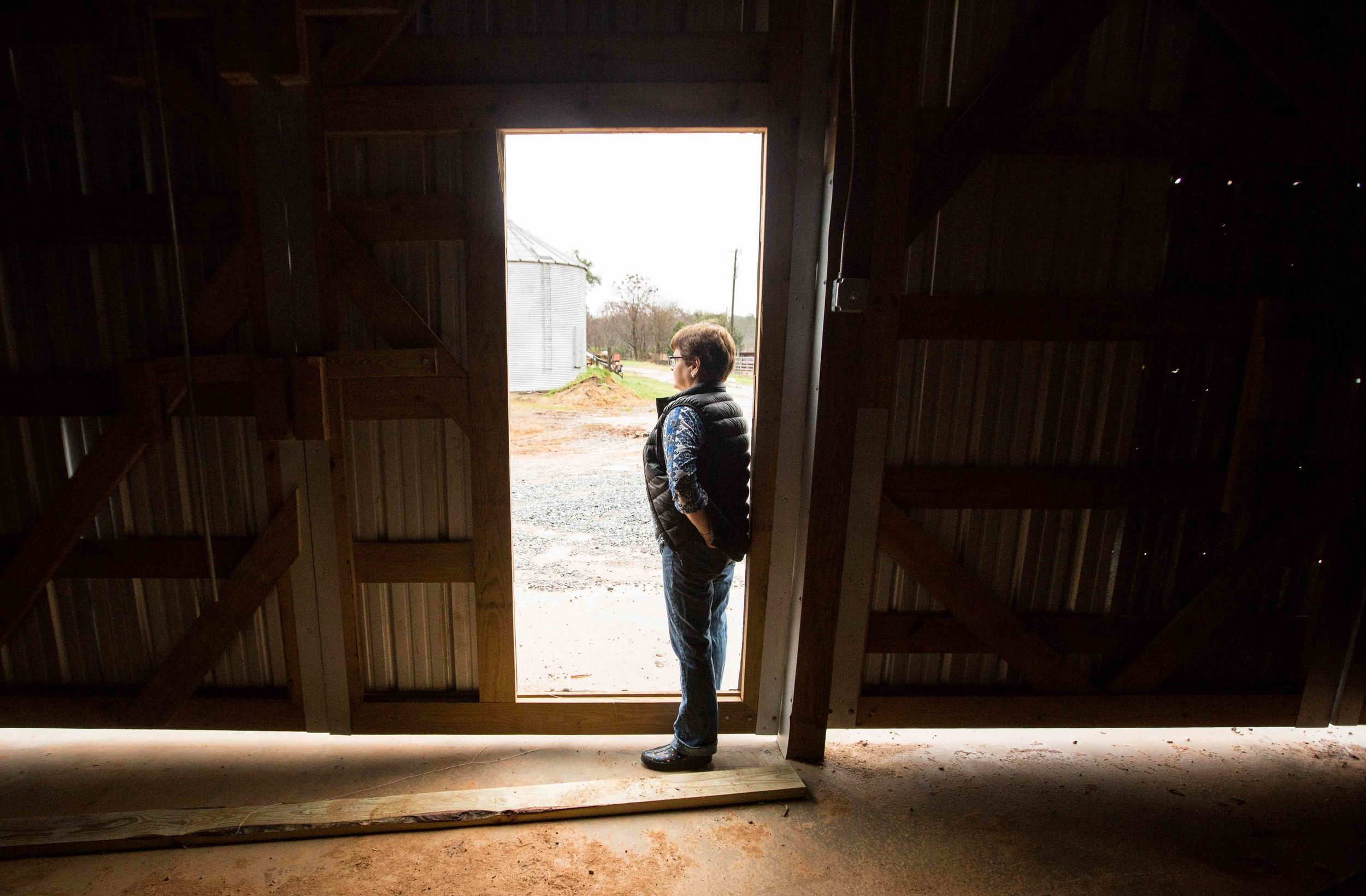 Farmer Melanie Sanders stands in the door a storage building on Buffalo Creek Straw and Seed Farm, Wednesday, Feb. 3, 2016, in Stephens, Ga. With over 42,000 farmers working in the Georgia agriculture industry, farming contributes over $73 Billion to Georgia's economy each year. Forecasters say profits are expected be down as well as exports in 2016 nationwide due to a fragile world economy. Photo by Branden Camp