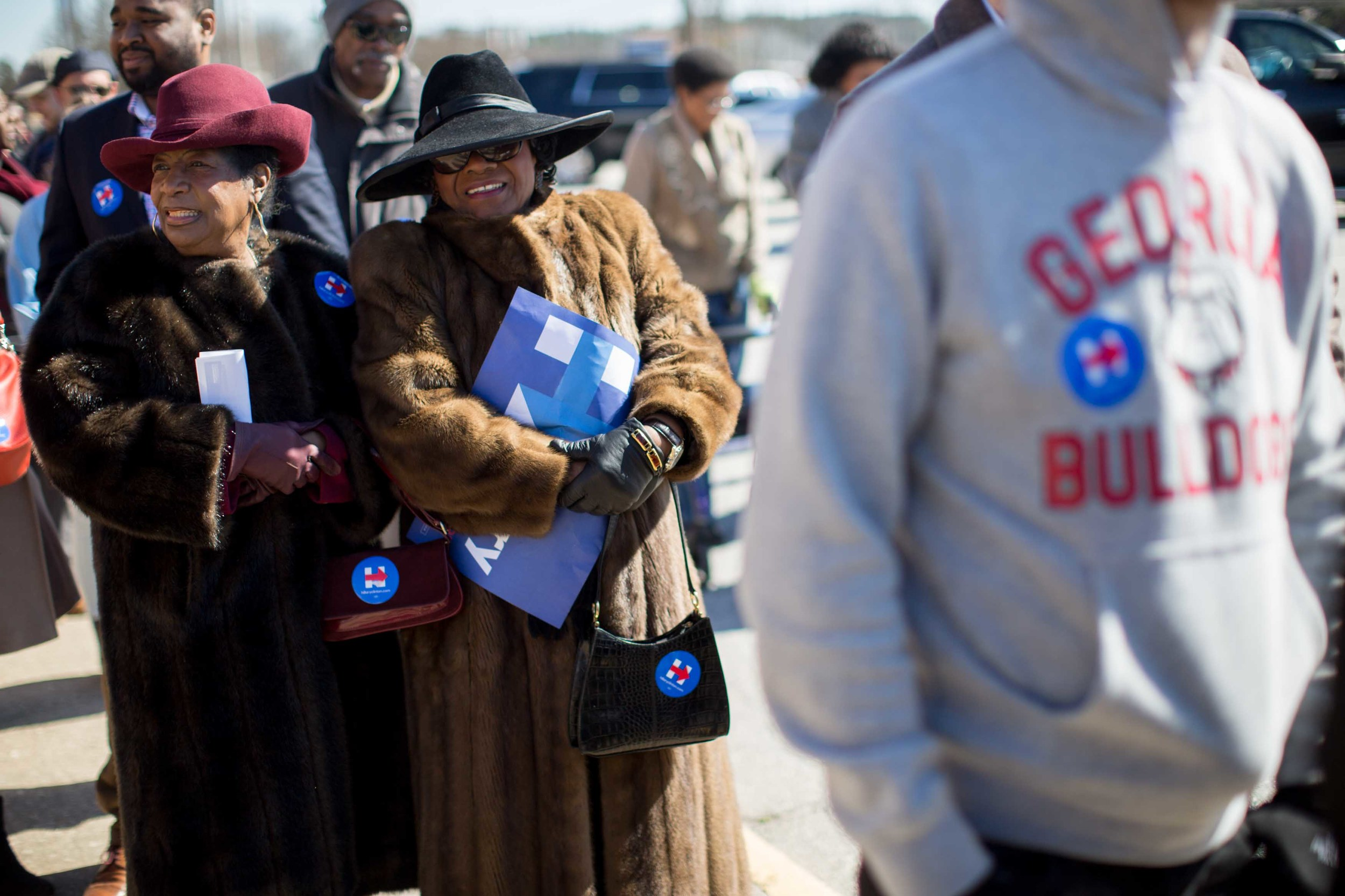 Bendolyn Ricks, left, and Anne McKenzie, center, wait in line to see former President Bill Clinton speak during a campaign stop for his wife, Democratic presidential candidate Hillary Clinton, at North Clayton High School.  Branden Camp/ZUMA Wire