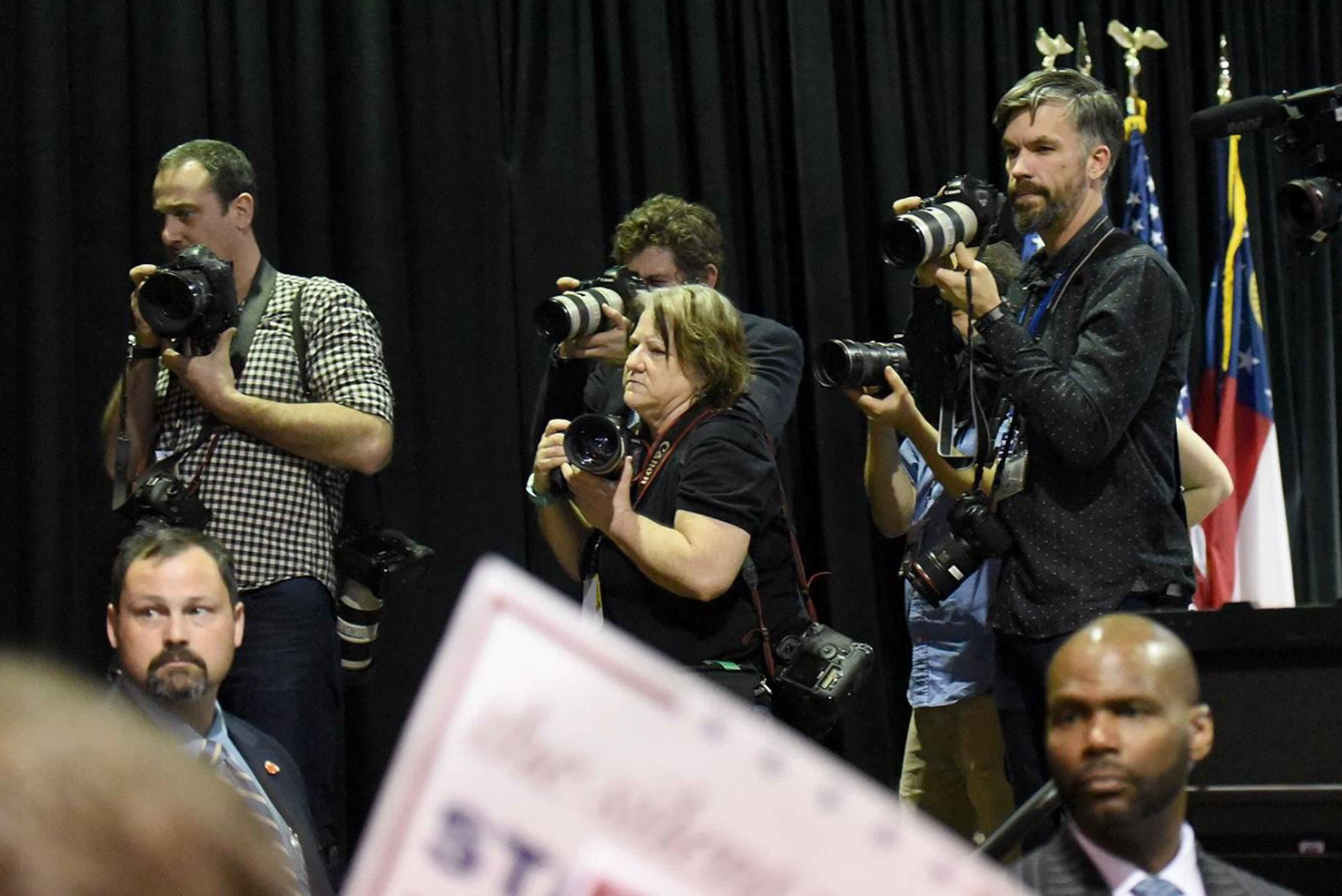 Associated Press photographer David Goldman, left, Getty Images freelance photographer Branden Camp (Me), center back, Reuters freelance photographer Tami Chappell, and New York Times freelance photographer Kevin D. Liles work from the stage as Republican candidate Donald Trump signs autographs for attendees in Atlanta.  Photo by Atlanta Journal-constitution photographer Hyosub Shin