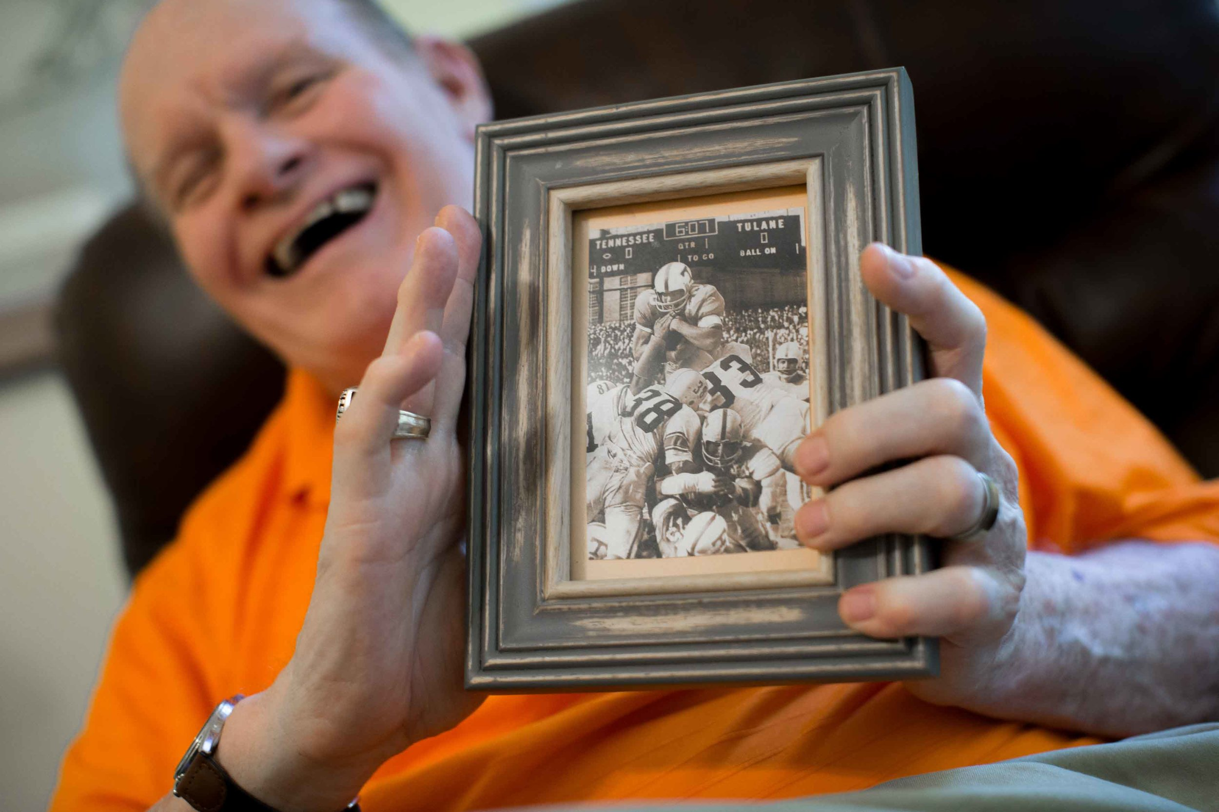 Walter Chadwick, who was a star running back at the University of Tennessee, poses for a portrait at his home while holding a photo of him scoring a touchdown during a game against Tulane University, Sunday, Aug. 28, 2016, in Decatur, Ga. Chadwick was named head coach of Wills High School in 1971, but after only being on the job just two weeks, a Wells Fargo armored van slammed into him leaving Chadwick permanently brain damaged. Chadwick recently gathered with friends and former students, many of whom thought he was dead. (Branden Camp for The Atlanta-Journal Constitution)