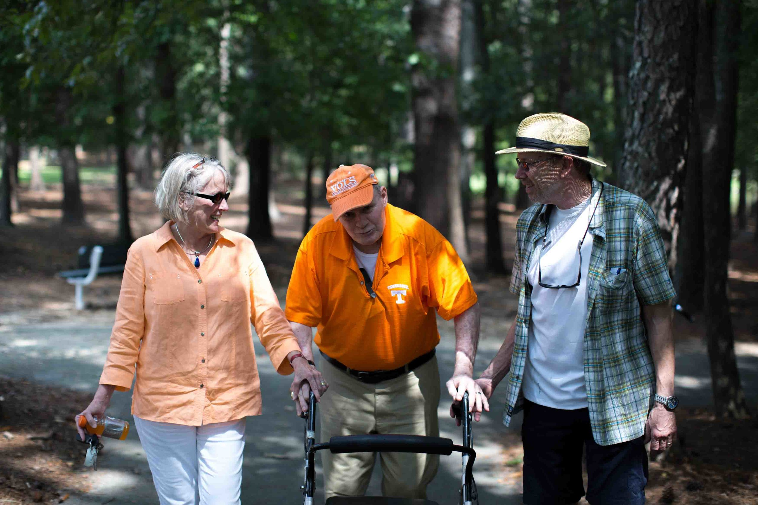 Walter Chadwick, center, who was a star running back at the University of Tennessee, walks with his friend and University of Tennessee alum Ellen Morrison, left, and former Wills High School football player Keith Miller in Laurel Park, Sunday, Aug. 28, 2016, in Marietta, Ga. Chadwick was named head coach of Wills High School in 1971, but after only being on the job just two weeks, a Wells Fargo armored van slammed into him leaving Chadwick permanently brain damaged. Chadwick recently gathered with friends and former students, many of whom thought he was dead.(Branden Camp for The Atlanta-Journal Constitution)