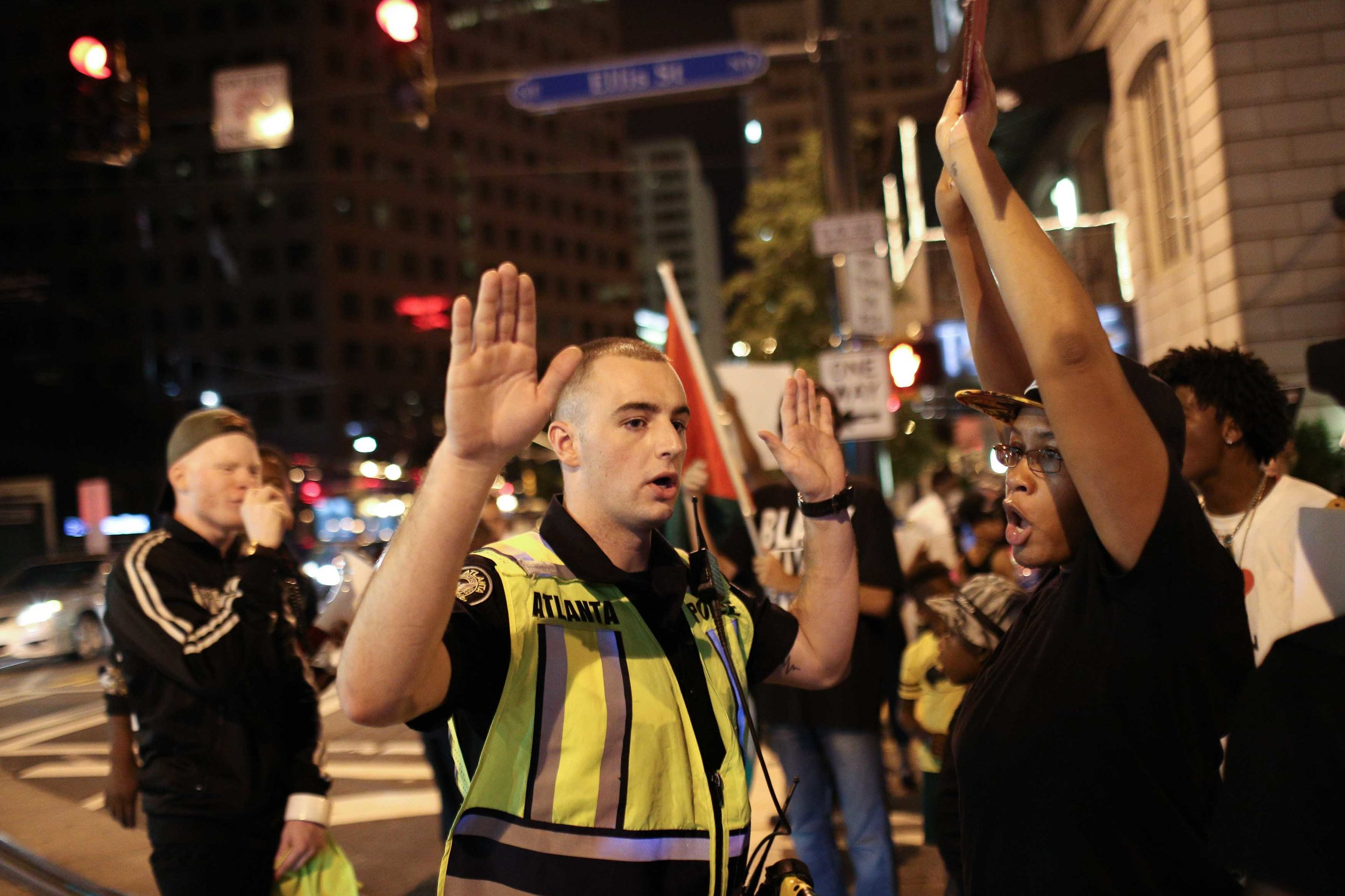 An Atlanta police officer tells Black Lives Matter protesters to move out of the street during a protest in downtown Atlanta, Saturday, Sept. 24, 2016. The protesters gathered in response to the police shooting deaths of Terence Crutcher in Tulsa, Okla. and Keith Lamont Scott in Charlotte, N.C.  (AP Photo/Branden Camp)