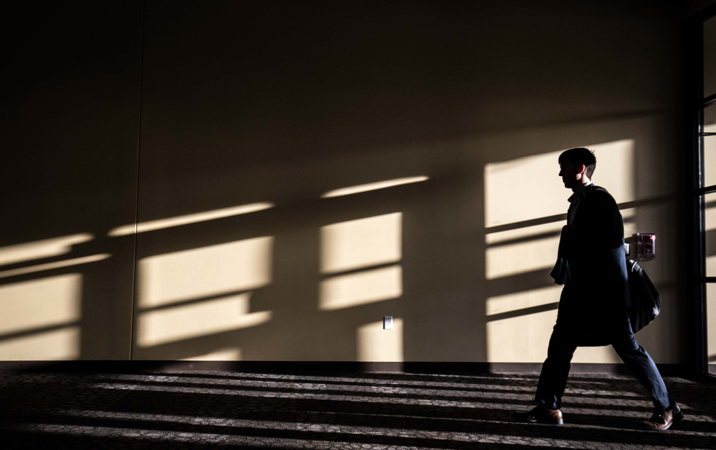A man walks through a church as sunlight shines on a wall in Indianapolis.  Photo by Branden Camp