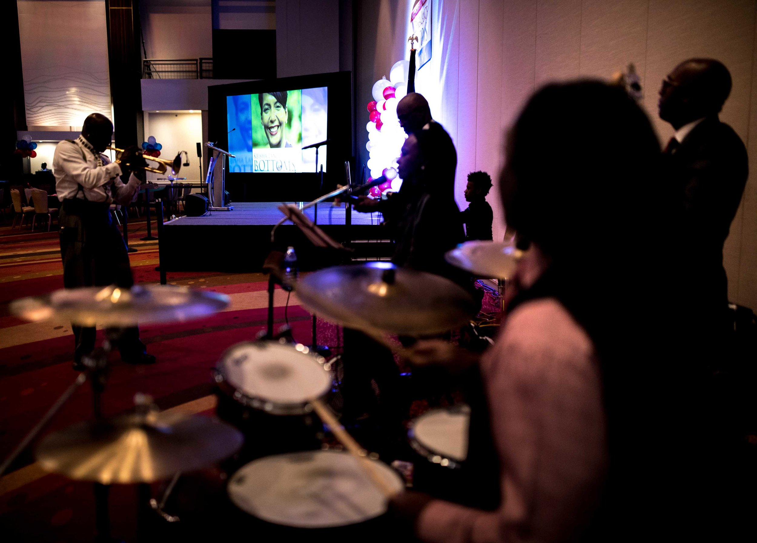 A photo of Keisha Lance Bottoms is displayed on a screen as a band warms up before an election party.