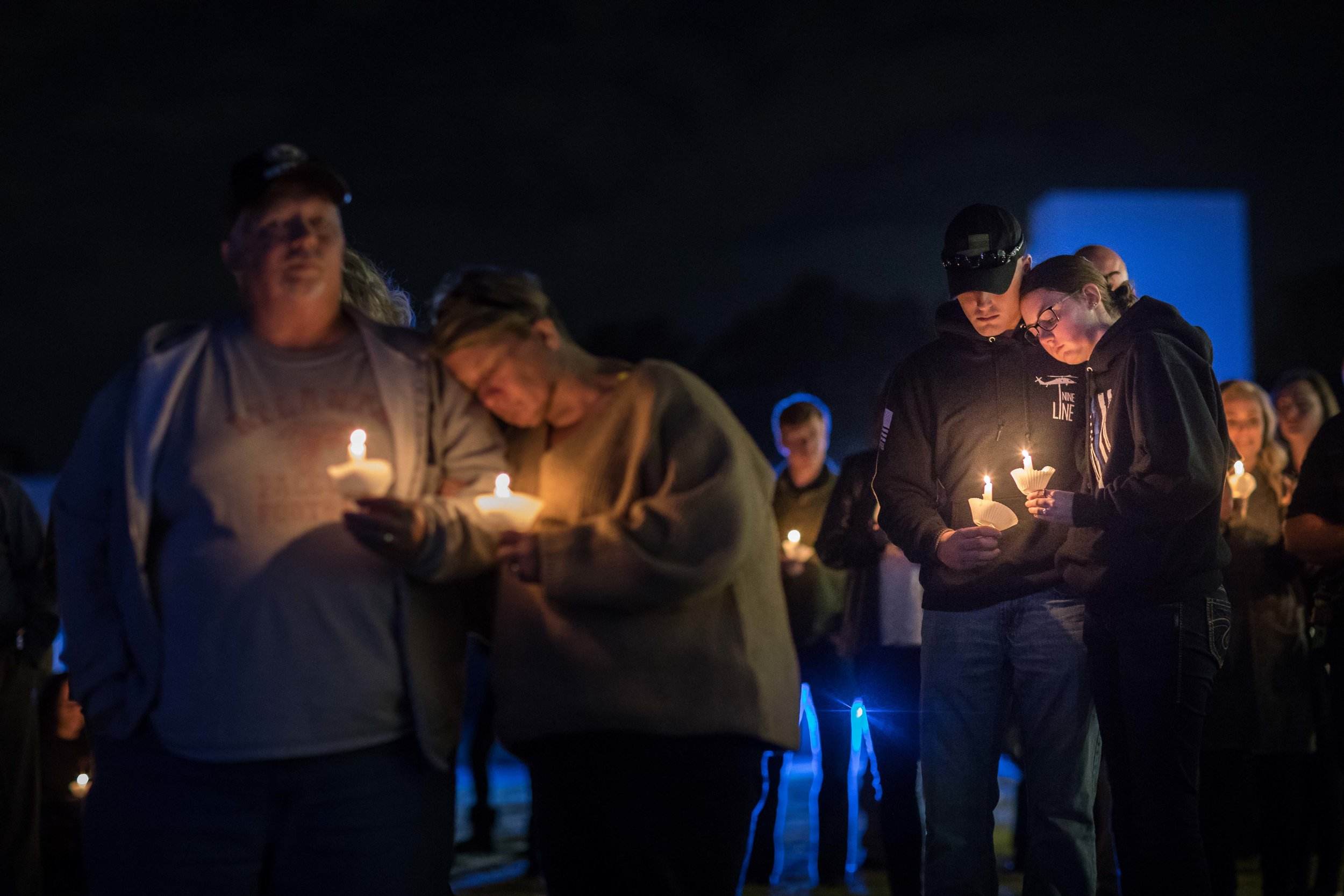 Police officers and members of the community hold candles during a vigil for Gwinnett police officer Antwan Toney, who was killed in the line of duty, at Gwinnett Church, Monday, Oct. 22, 2018, in Sugar Hill, Ga. A Gwinnett County police officer on Monday shot and killed Maynard, 18, accused of fatally shooting police officer Antwan Toney on Saturday near a school in the Atlanta area, police said. (Branden Camp/Atlanta Journal-Constitution via AP)