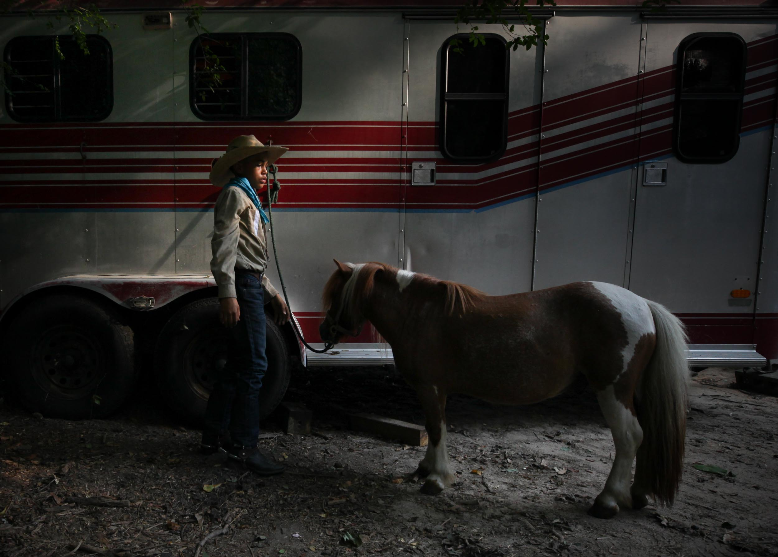 Logan Dansby, 12, prepares to clean a pony on a ranch off of Flat Shoals Parkway, Tuesday, July 30, 2019, in Union City. Branden Camp for AJC