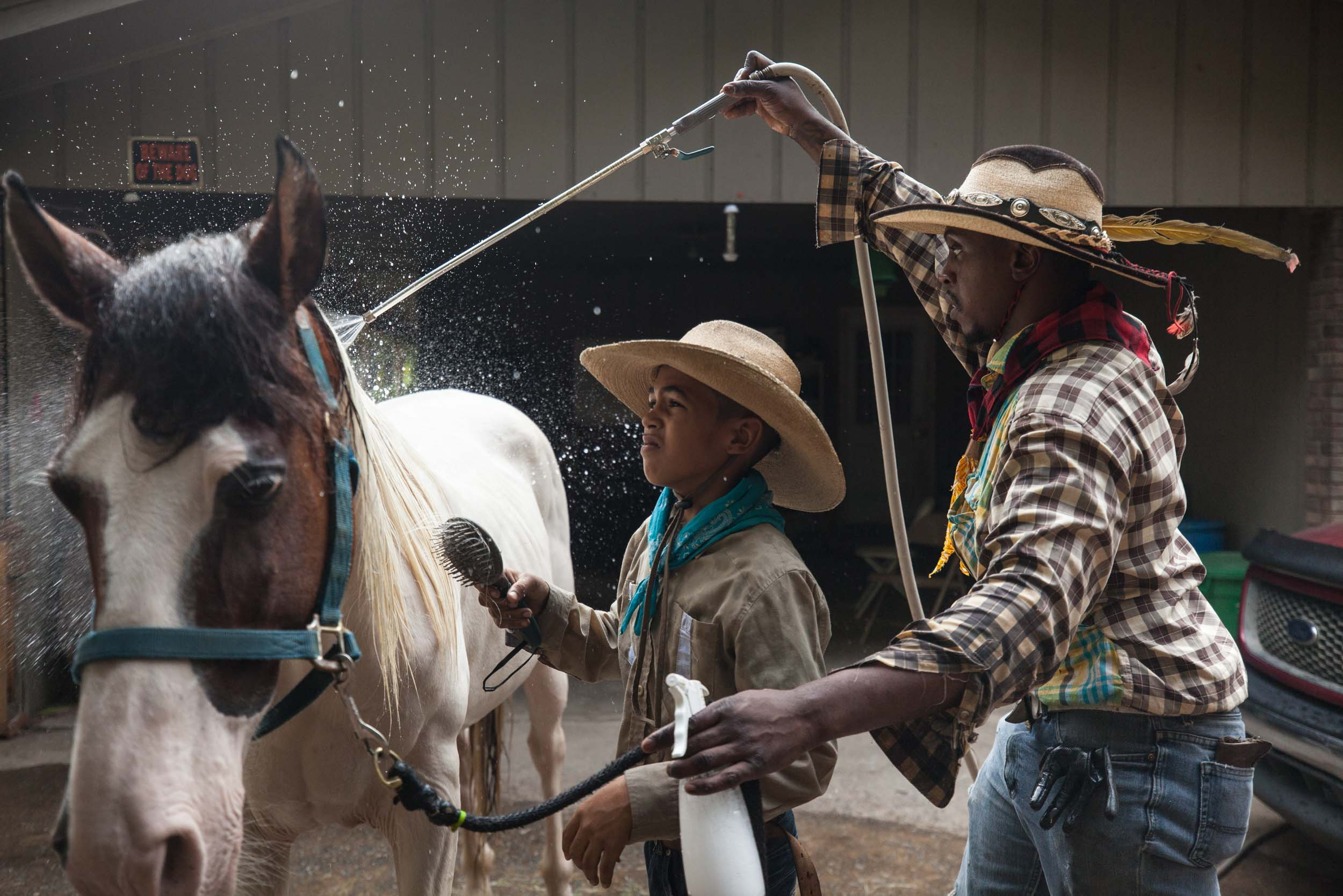 Arkansas Dave and his son Logan Dansby, 12, clean a horse on a ranch off of Flat Shoals Parkway, Tuesday, July 30, 2019, in Union City. Branden Camp for AJC