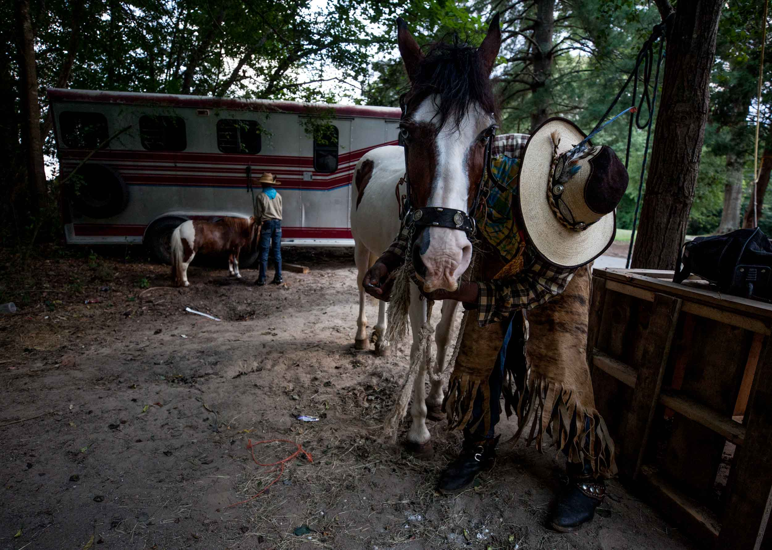 Arkansas Dave, right, cleans his horse while is son, Logan Dansby, 12, ties up his pony on a ranch off of Flat Shoals Parkway, Tuesday, July 30, 2019, in Union City, Ga. Branden Camp for AJC