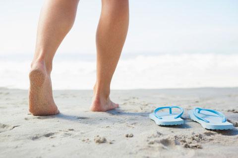 woman-legs-walking-on-sandy-beach-with-flip-flops