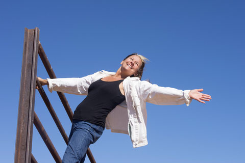 older-woman-outstretched-hands-on-climbing-frame