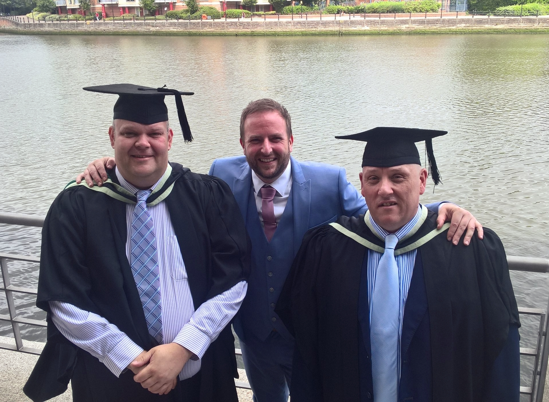 Aaron and David celebrate their graduation with Stephen Marks from Supporting Communities.