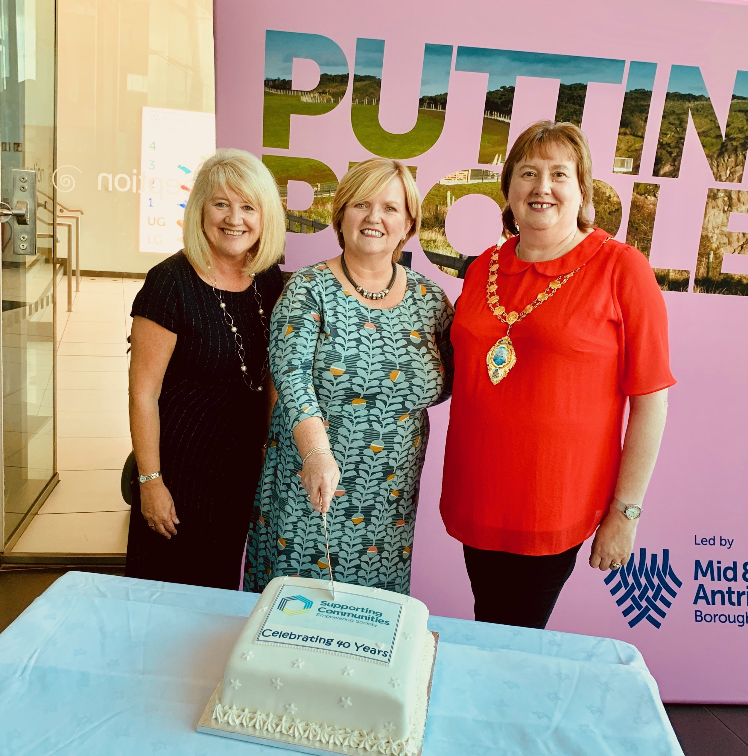 Lorraine Campbell, Theresa Patton, and Cllr. Maureen Morrow make it official with an anniversary cake!