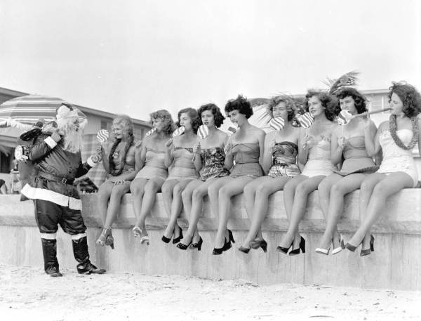 Santa Claus handing out treats to nine young women on the beach: Saint Petersburg, Florida. Date: 1952 Physical descrip: 1 photoprint - b&w - 4 x 5 in. Series Title: Department of Commerce collection Repository: State Library and Archives of Florida, 500 S. Bronough St., Tallahassee, FL 32399-0250 USA. Contact: 850.245.6700. Archives@dos.state.fl.us