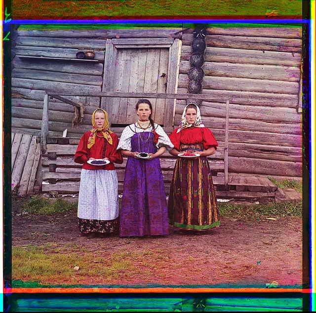 "Three young women offer berries to visitors to their izba, a traditional wooden house, in a rural area along the Sheksna River, near the town of Kirillov.   ""Peasant girls"" from The Library of Congress. Russian Empire [1909] 1 negative (3 frames) : glass, b&w, three-color separation ; 24 x 9 cm. Forms part of: Sergei Mikhailovich Prokudin-Gorskii Collection (Library of Congress)."