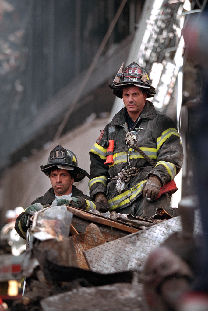 Firefighters look on Friday, Sept. 14, 2001, as President George W. Bush surveys the destruction left by terrorist attacks on New York City. From the US National Archives.