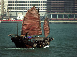 Image 1  is the source image with a base grade applied. The traditional junk gets confused with the modern background, so color enhancement is needed to emphasize the beauty of the boat and to compare it against the architecture.