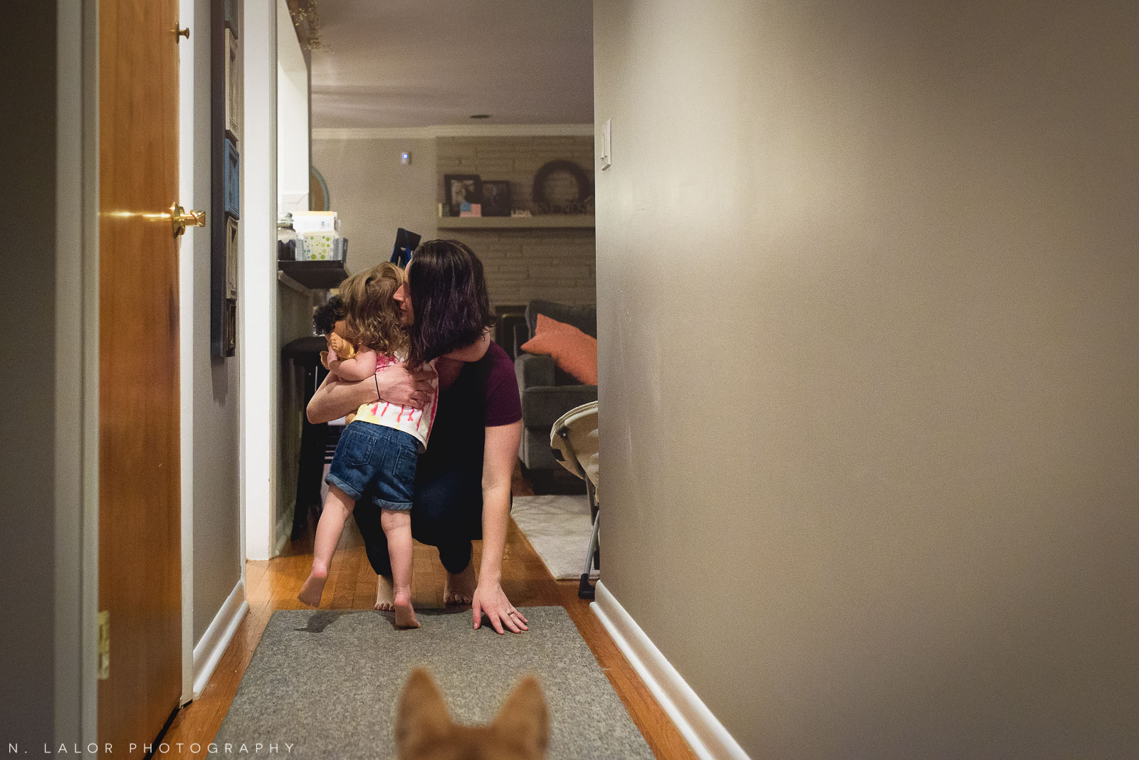 2-year old girl gives Mom early morning hugs in the hallway. Documentary photo by N. Lalor Photography.