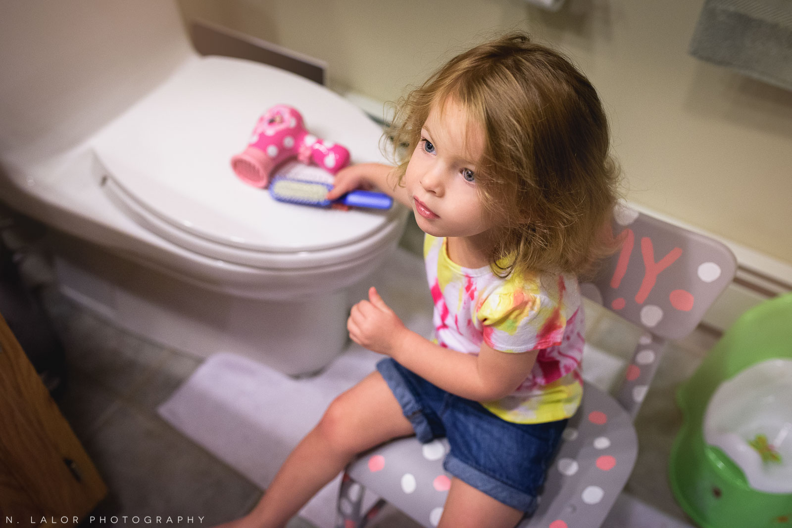 2-year old girl watching Mom get ready in morning. Documentary photo by N. Lalor Photography.