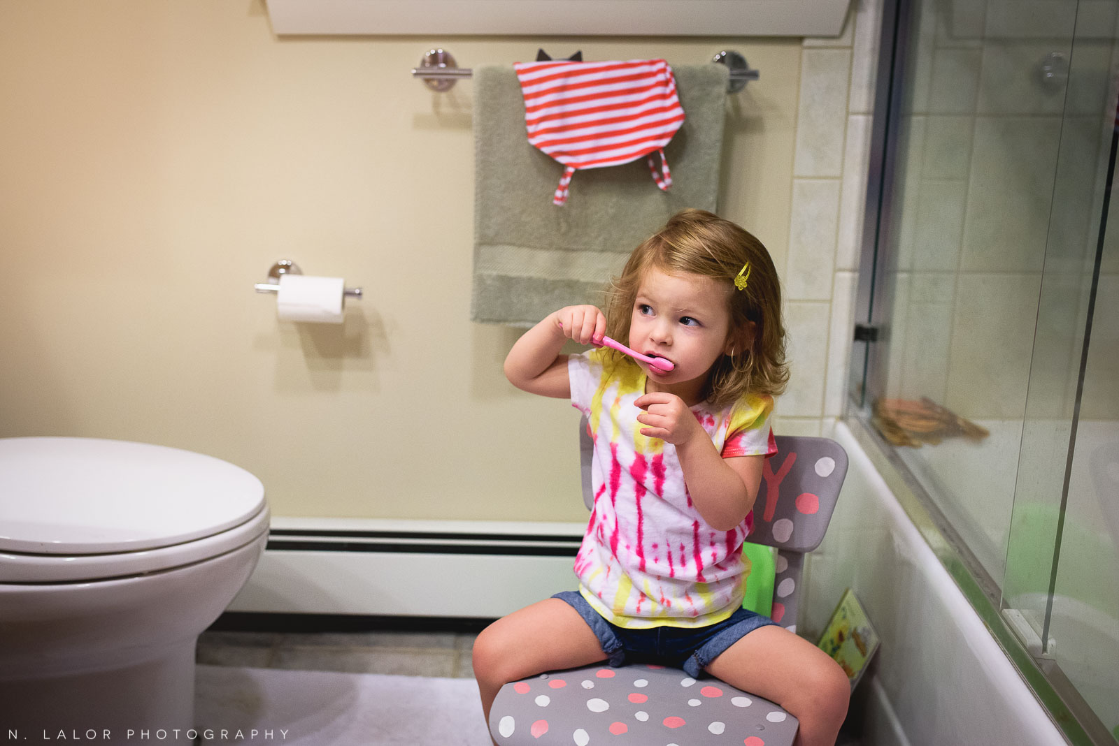 2-year old girl brushing teeth in the morning. Documentary photo by N. Lalor Photography.