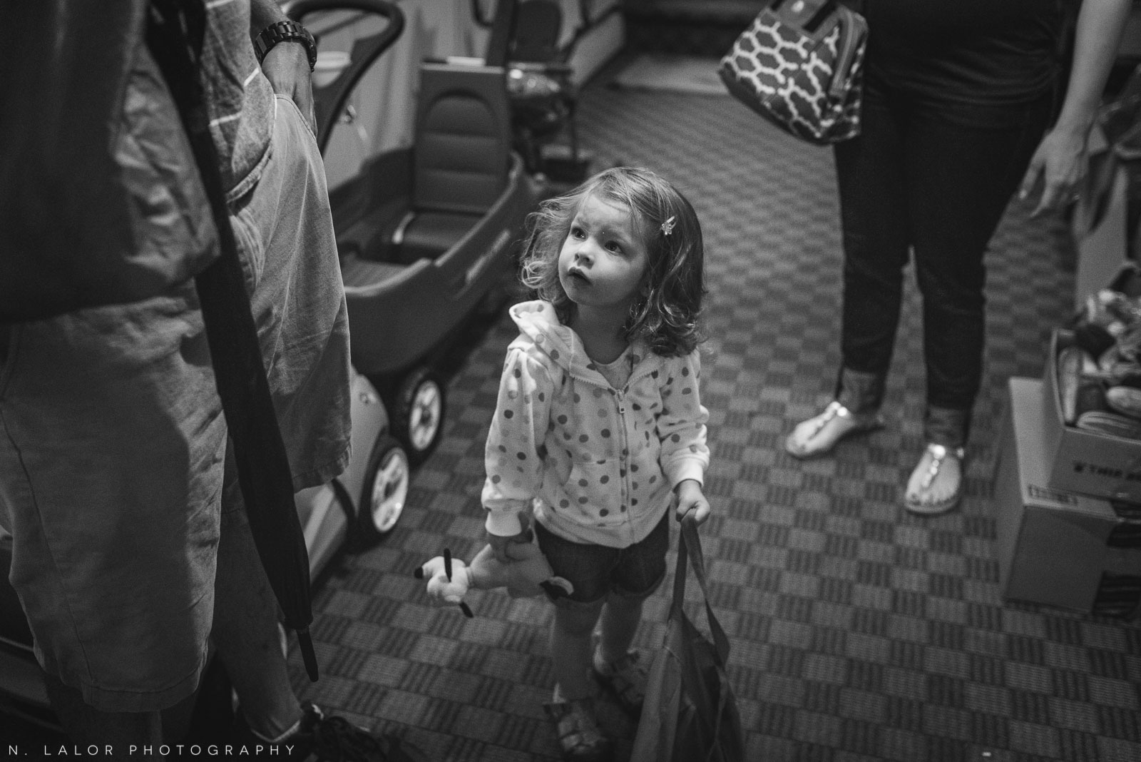 2-year old girl getting ready to step outside into the rain with her parents. Documentary photo by N. Lalor Photography.