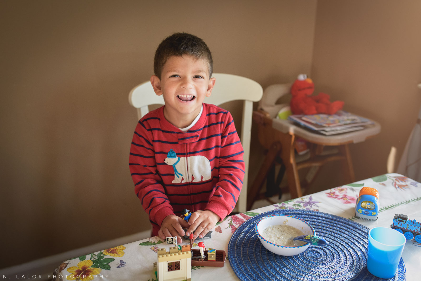 Avoiding breakfast. 4-year old boy plays with Legos at the table. Documentary photo by N. Lalor Photography.