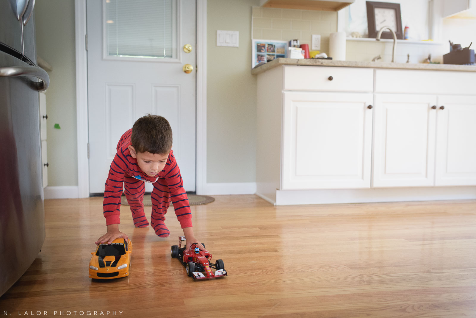 4-year old boy playing with cars on the kitchen floor. Documentary photo by N. Lalor Photography.