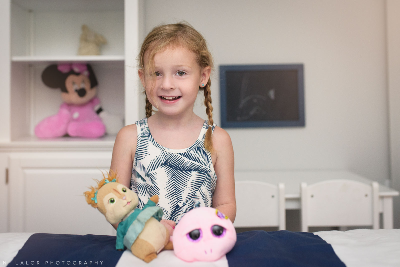4-year old girl showing off her favorite stuffed toys in her room. Lifestyle portrait by N. Lalor Photography.