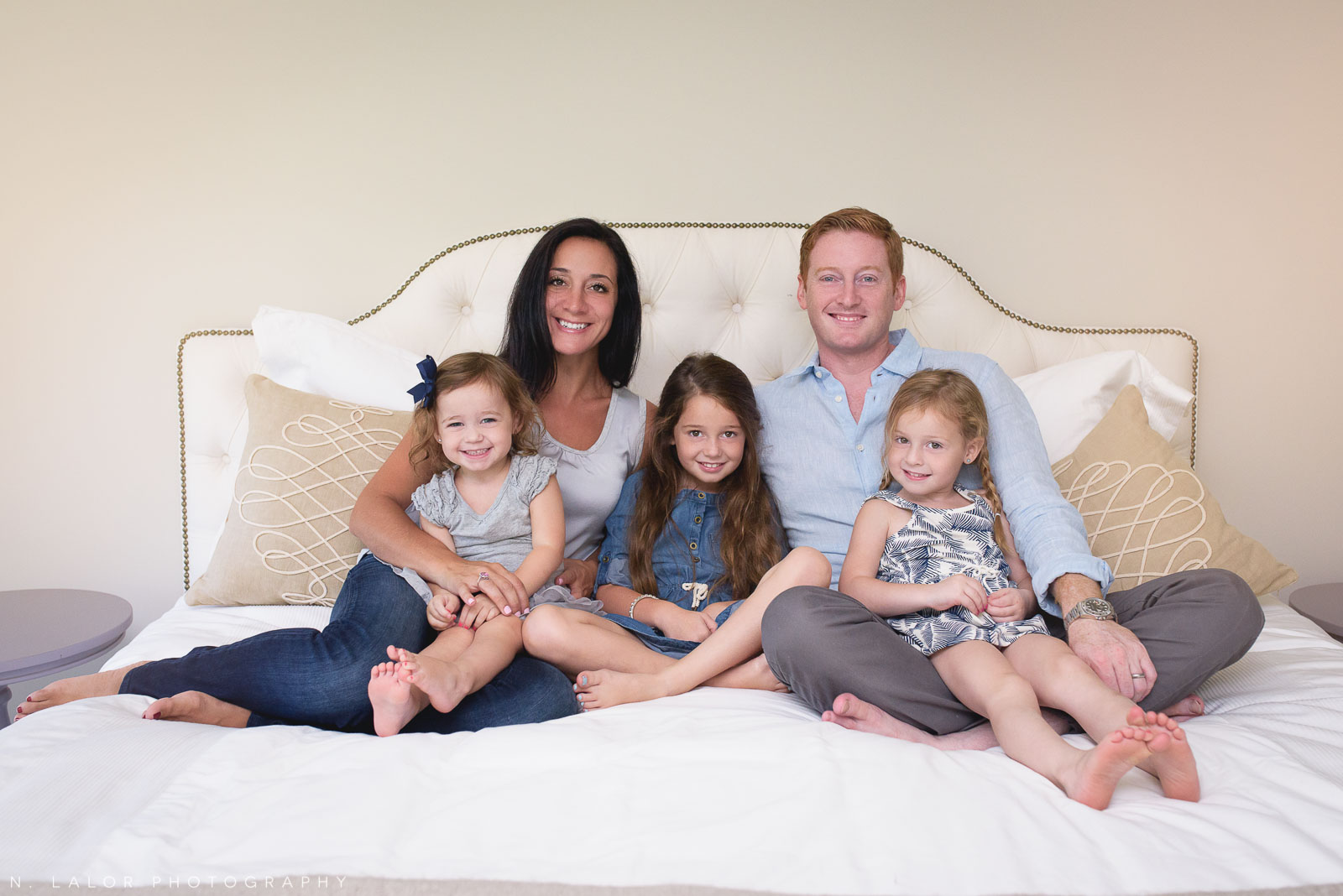 A lifestyle photo of a happy smiling family of 5. Naturally styled family photo by N. Lalor Photography.