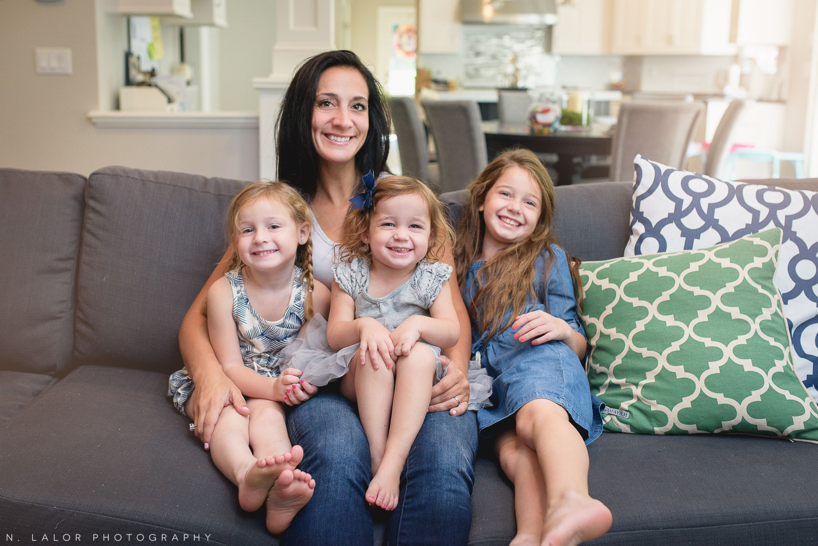 Mom with her three daughters, snuggling on the couch. Lifestyle portrait by N. Lalor Photography.