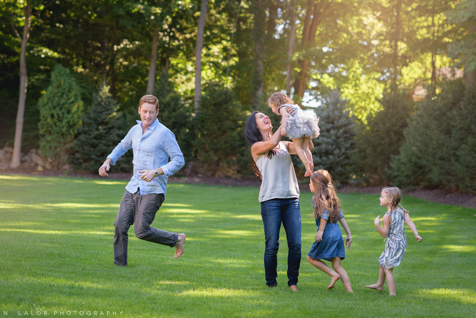Candid family photo of everyone running around and being silly. Lifestyle portrait by N. Lalor Photography.