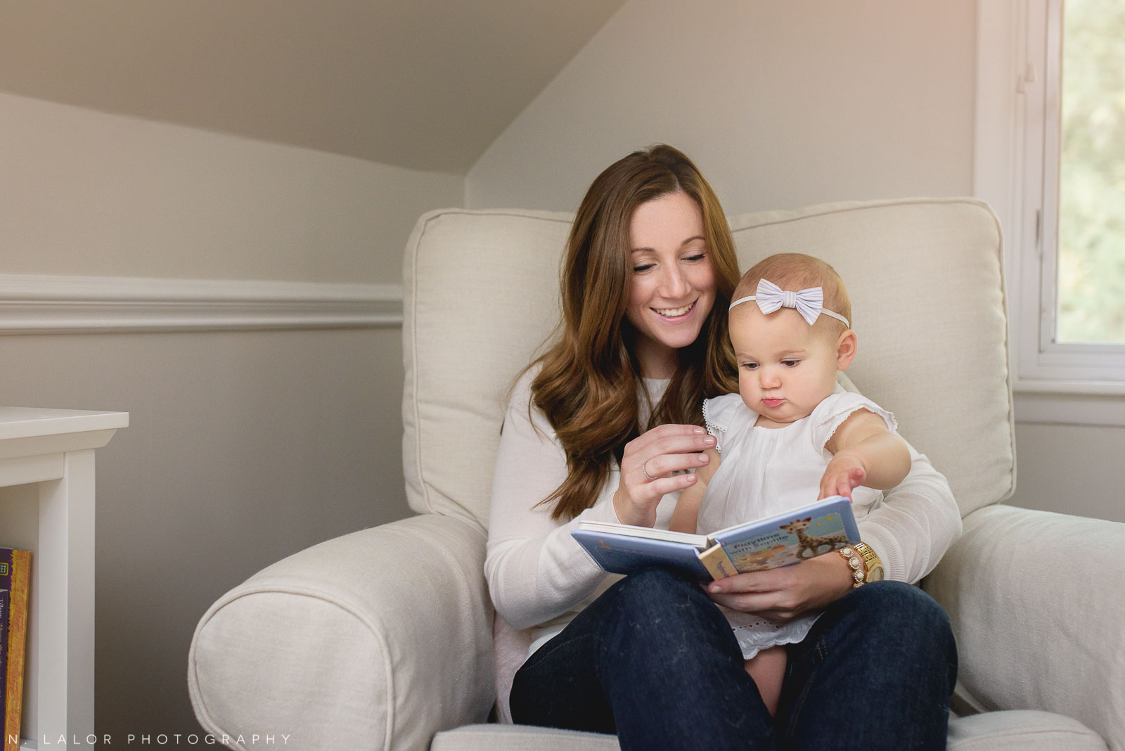 Baby girl reading in the rocking chair with mama. Naturally styled family portrait by N. Lalor Photography.