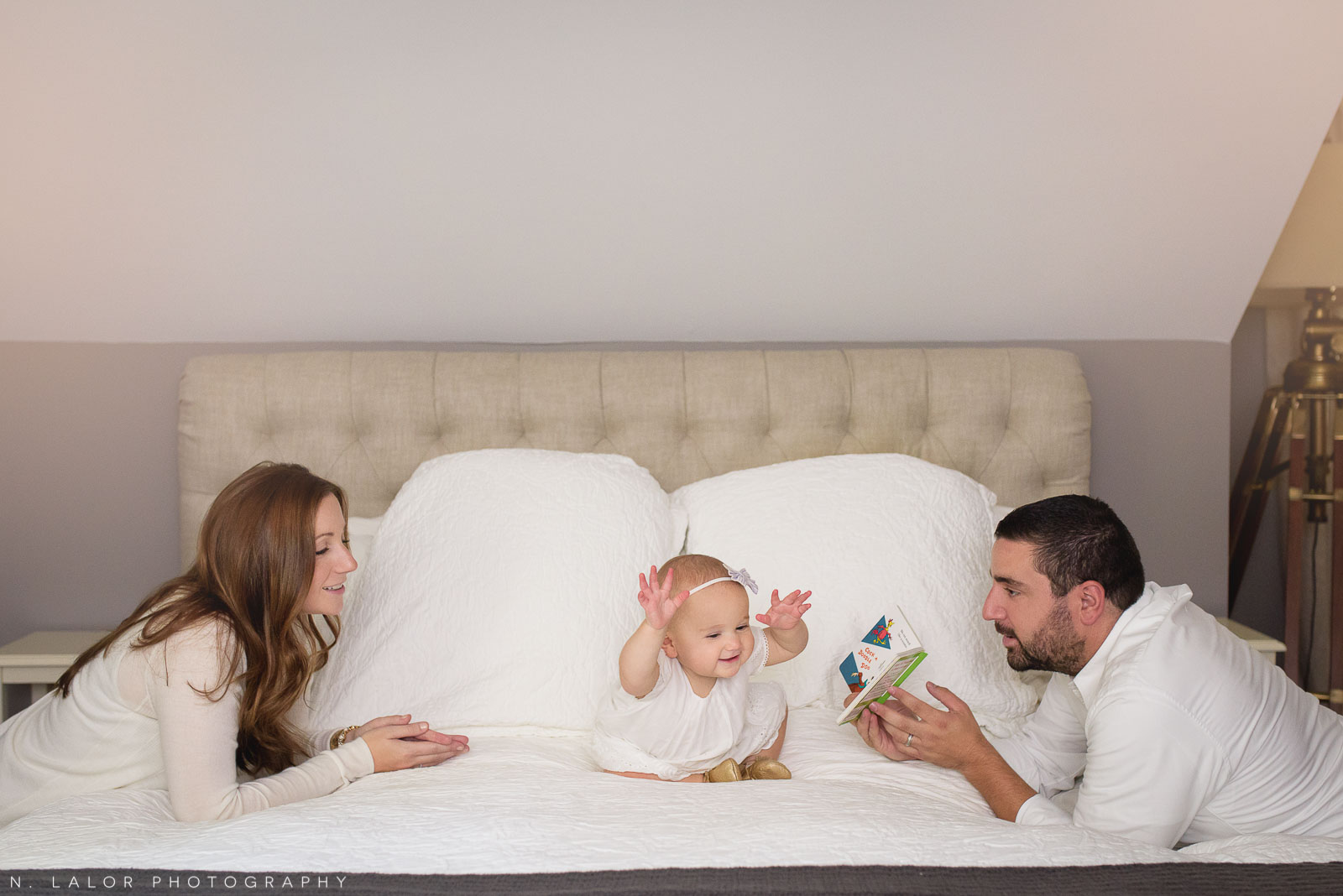 Parents playing on the bed with their 1-year old daughter. Naturally styled family portrait by N. Lalor Photography.