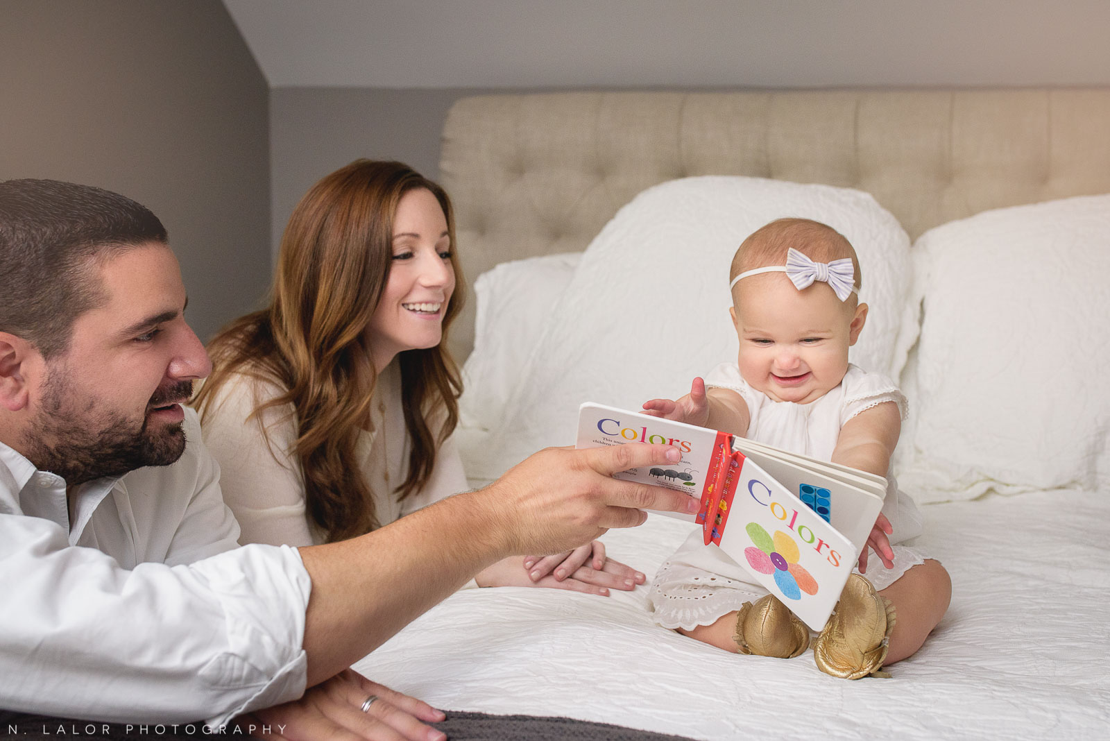 Parents having fun and reading with their 1-year old daughter. Lifestyle family portrait by N. Lalor Photography.