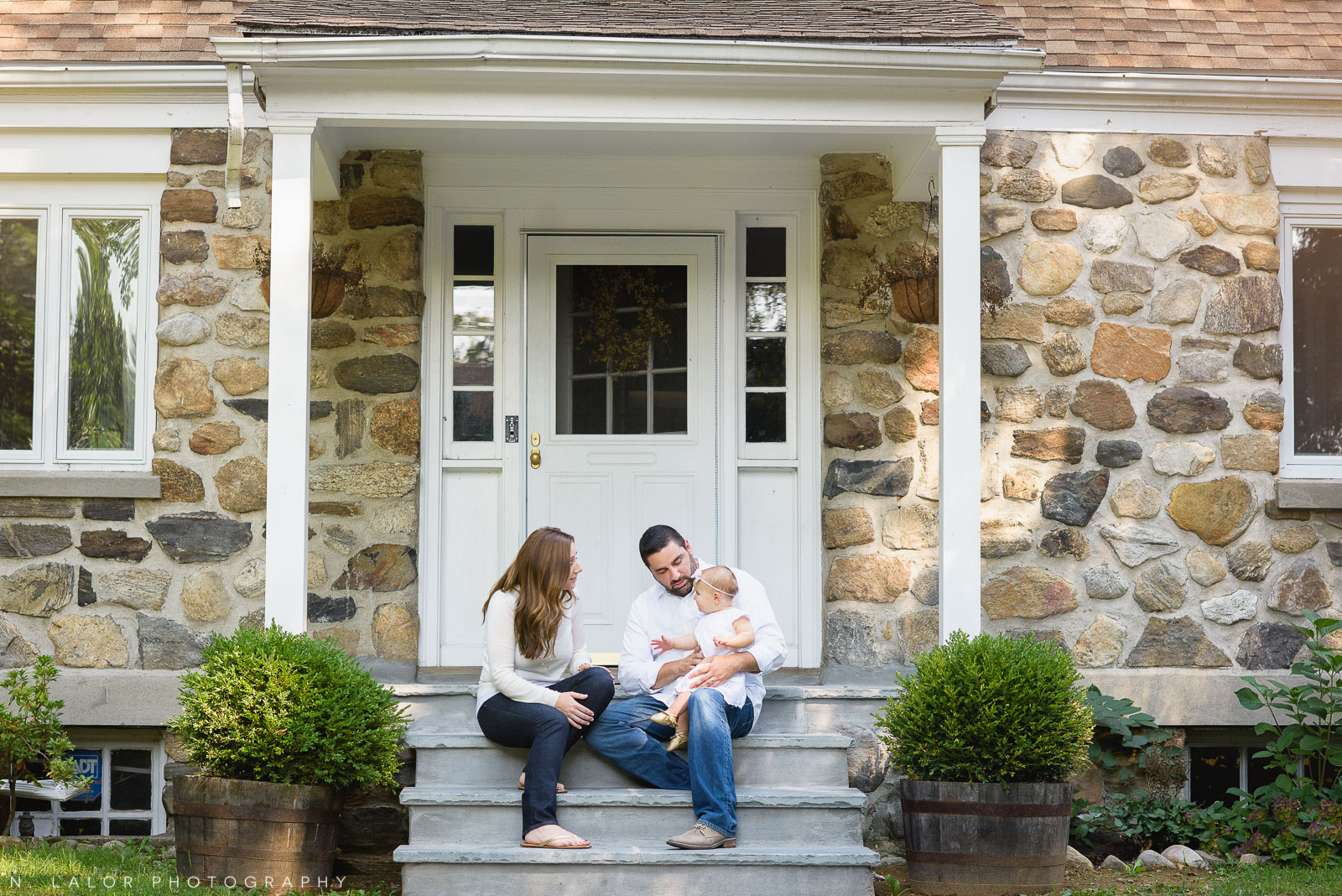 Lifestyle family portrait in front of their lovely home in Katonah, NY. Photo by N. Lalor Photography.