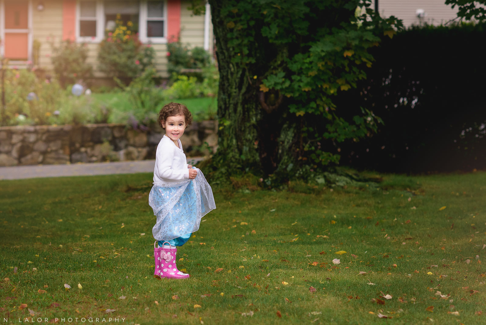 Elsa wearing rain boots. A mini dress-up photo session in Fairfield County, CT by N. Lalor Photography.