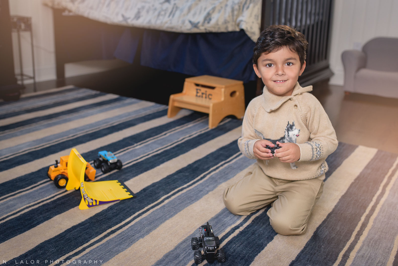 Boy playing with trucks in his room. Lifestyle portrait by N. Lalor Photography.