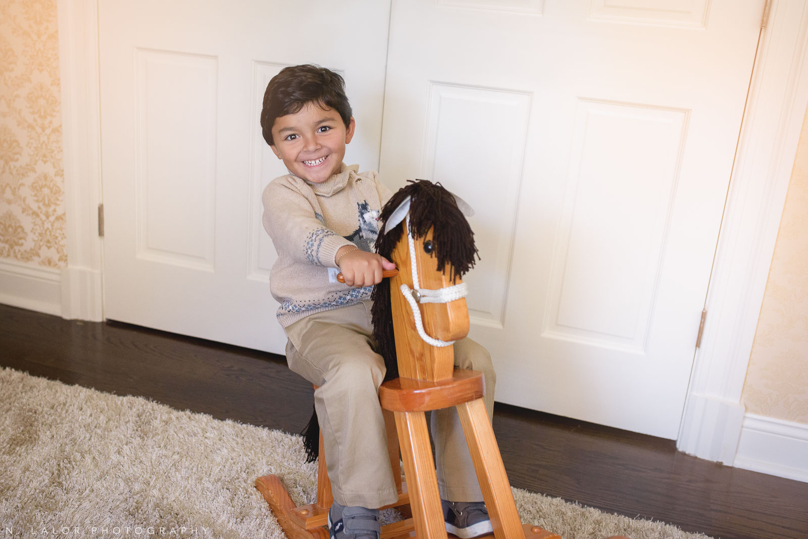 Happy smiling 4-year old boy on a rocking horse. Lifestyle portrait by N. Lalor Photography.