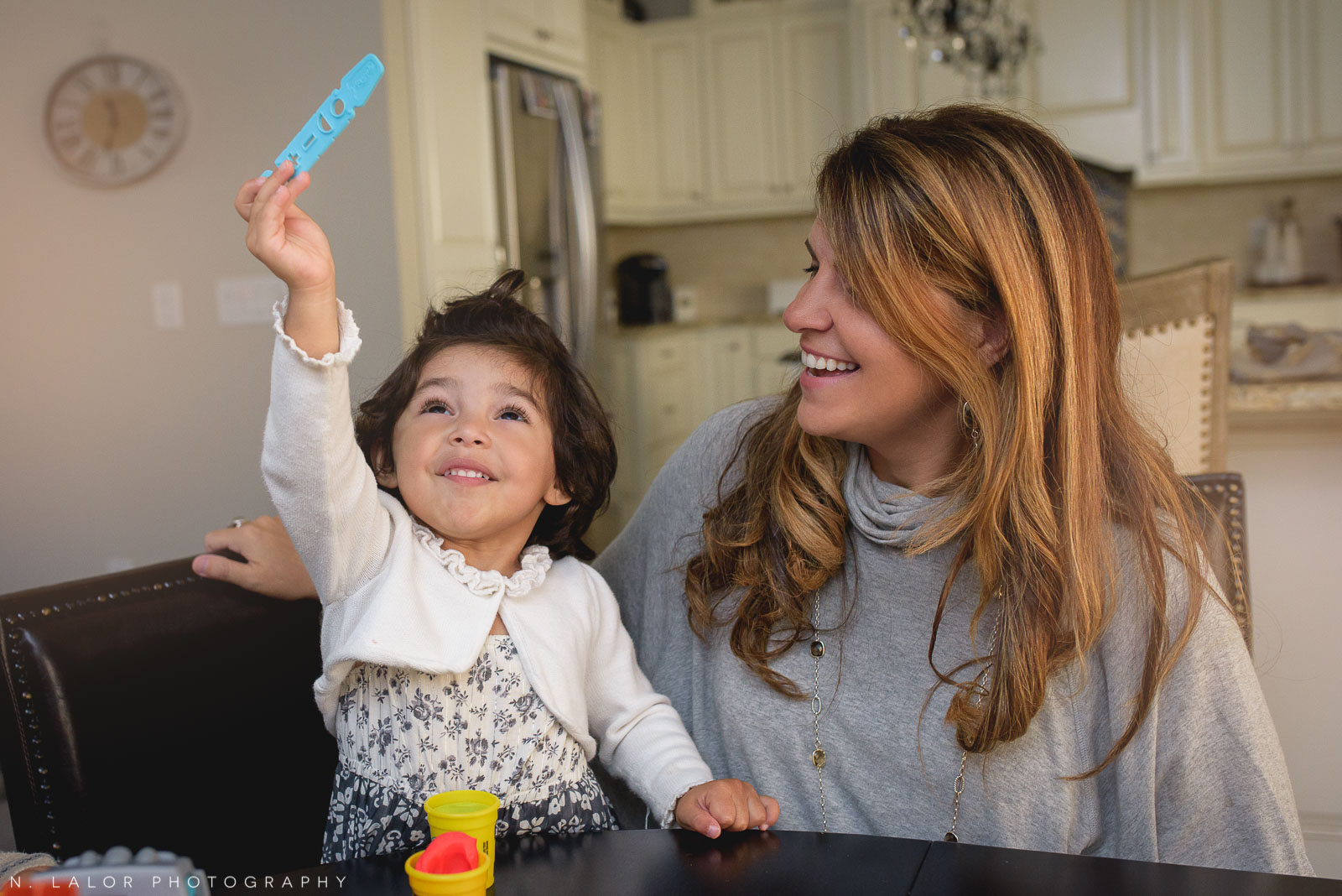 Happy smiling little girl playing play-doh with her Mom. Lifestyle portrait by N. Lalor Photography.