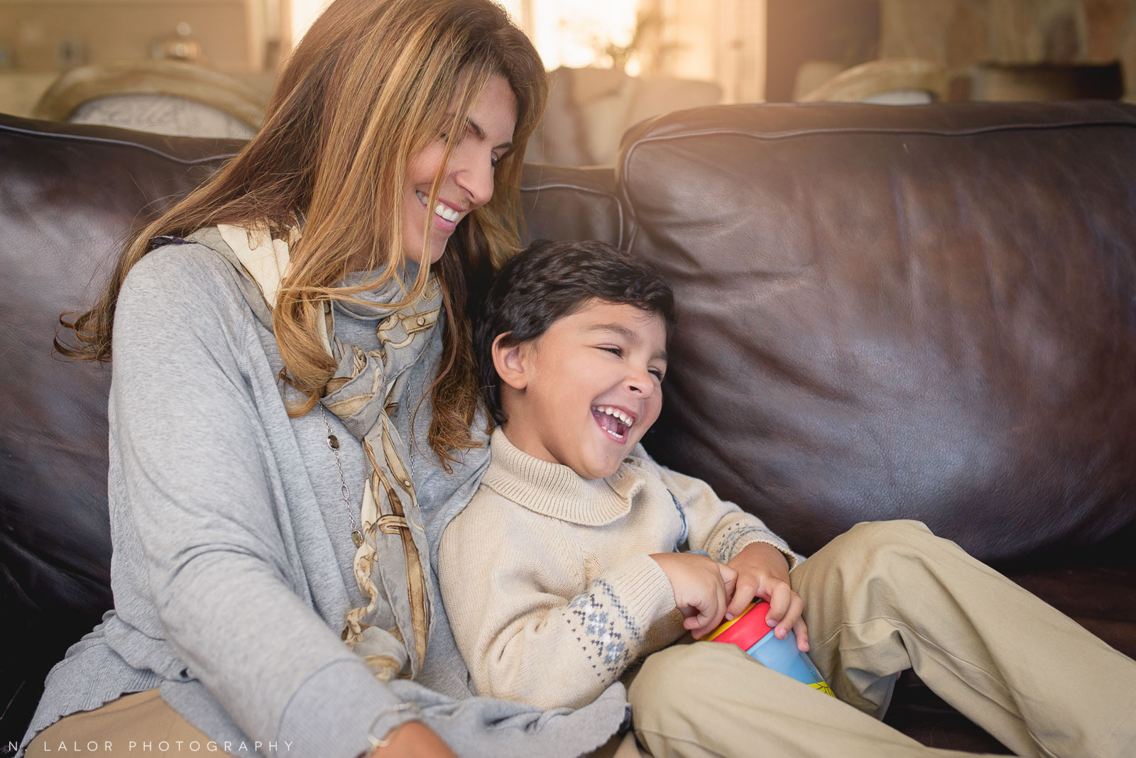 Mom and her son laughing on the couch. Lifestyle portrait by N. Lalor Photography.