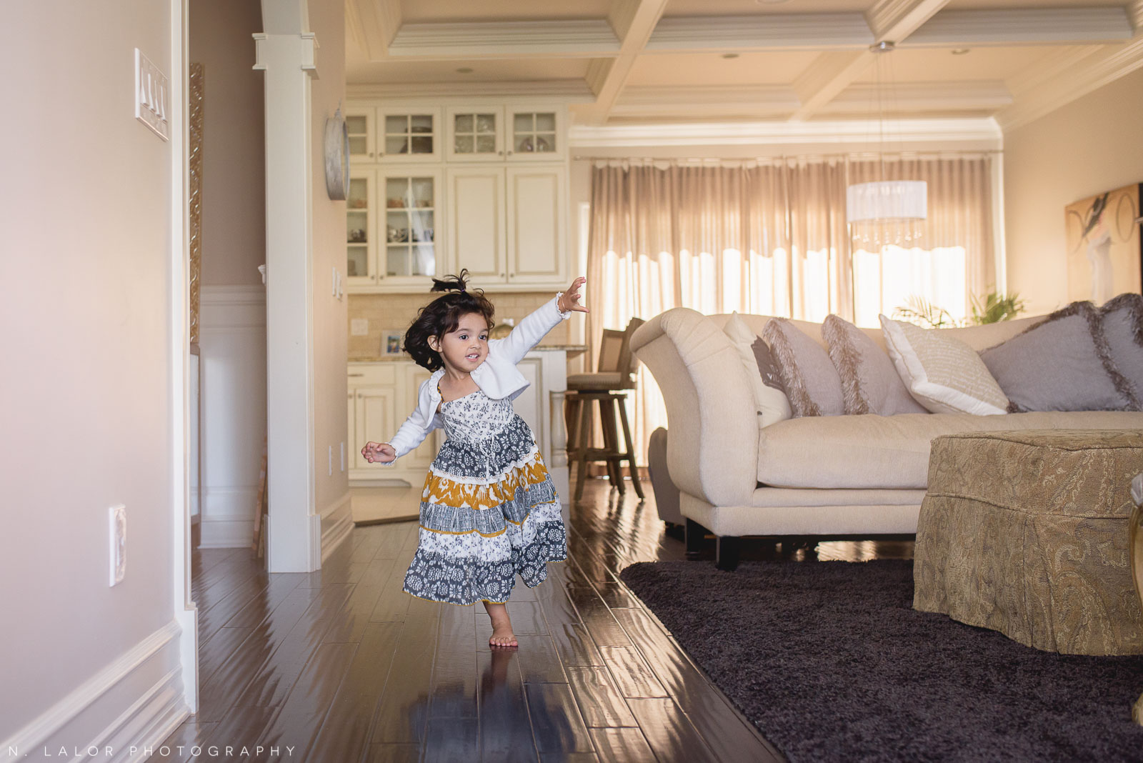 Happy little girl running around in her living room. Lifestyle portrait by N. Lalor Photography.