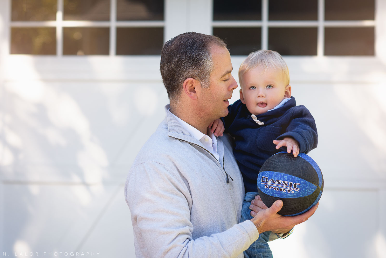 1-year old Son with Dad, playing basketball. Lifestyle portrait by N. Lalor Photography.