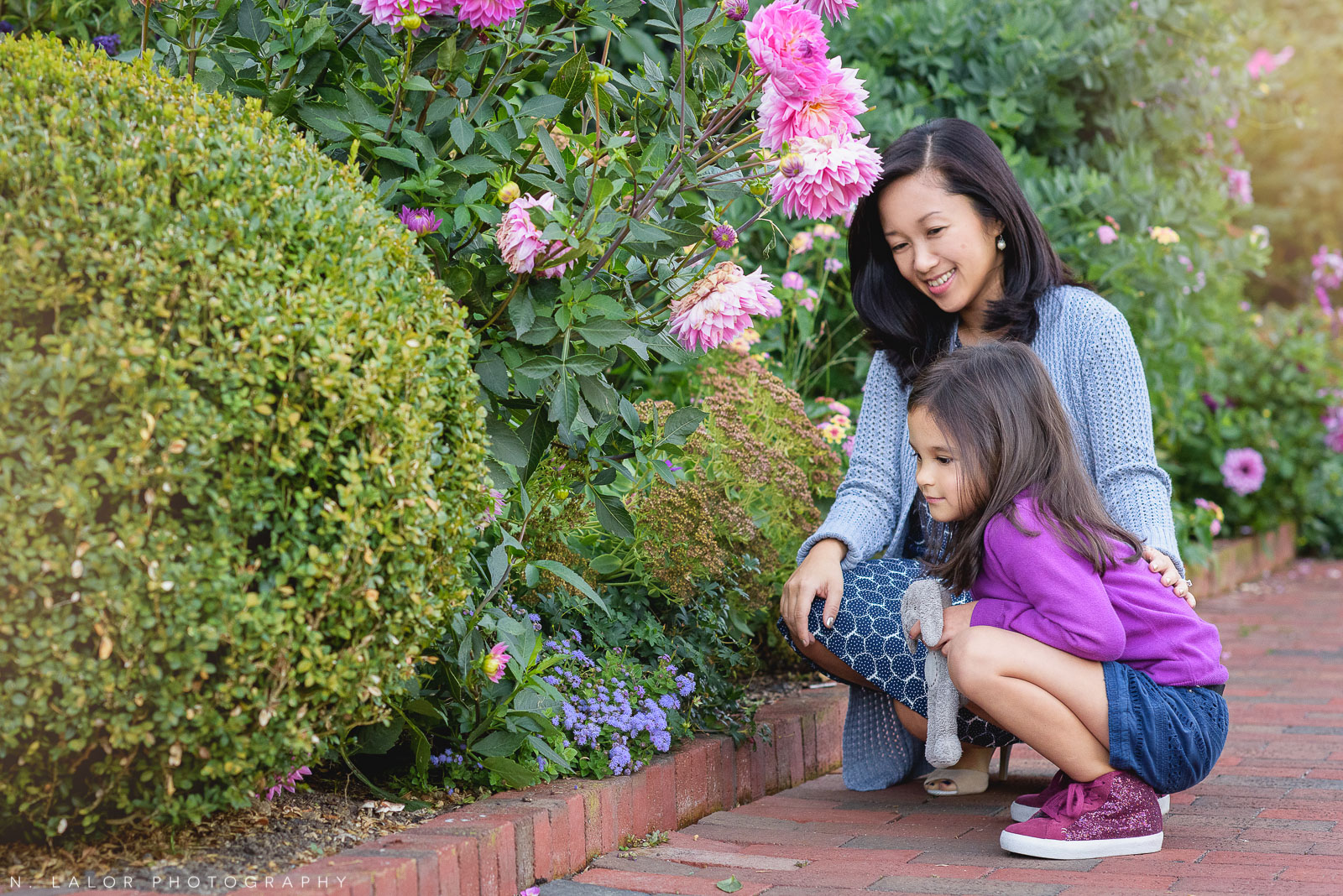 Lifestyle portrait of Mom and daughter looking at beautiful flowers in the garden. Photo by N. Lalor Photography. Waveny Park, New Canaan, Connecticut.