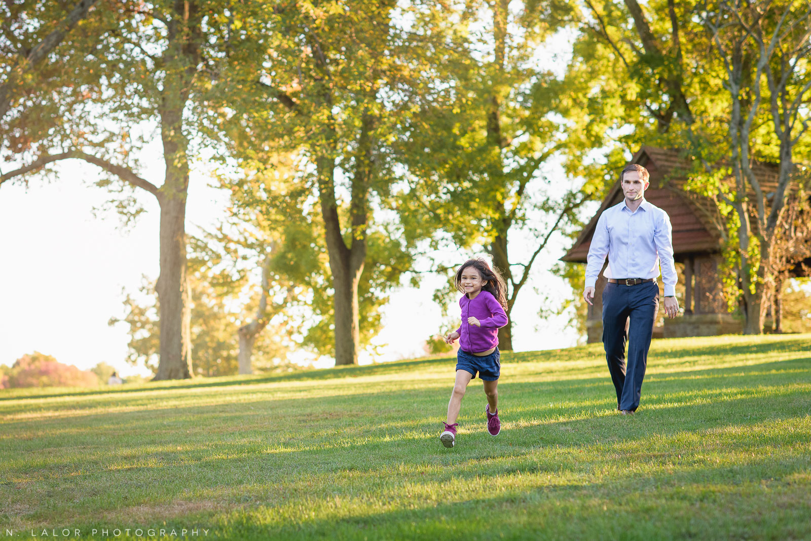 Father daughter lifestyle portrait in a grassy field by N. Lalor Photography. Waveny Park, New Canaan, Connecticut.