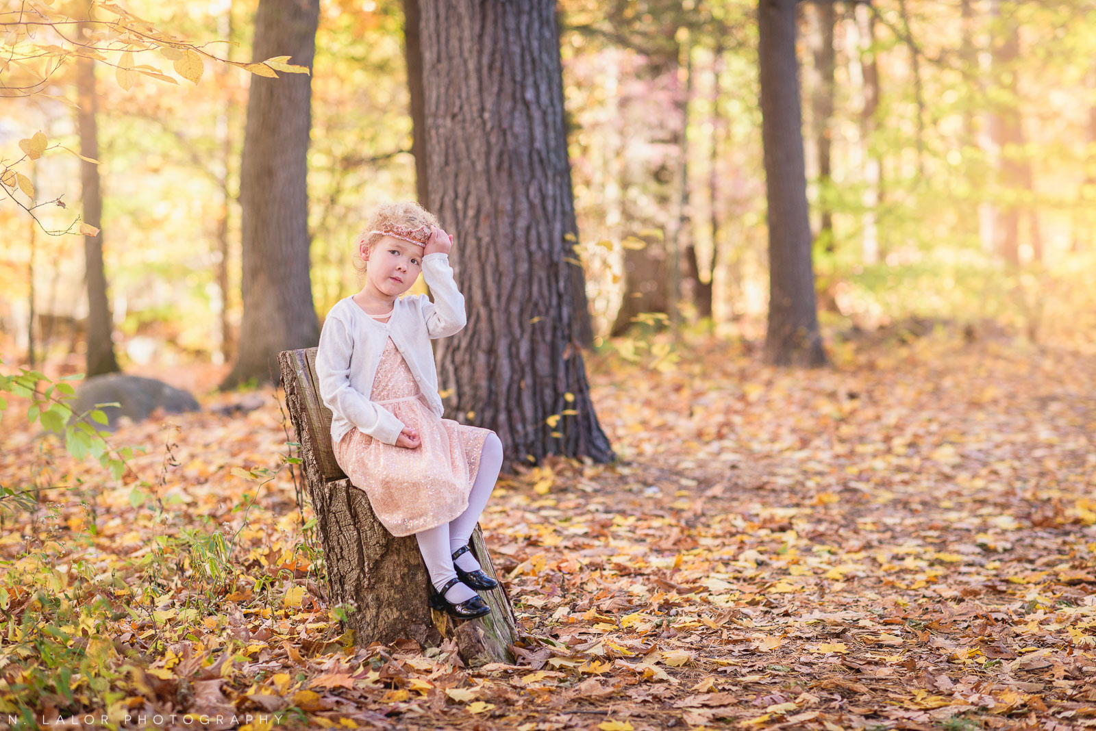 4-year old girl adjusting her crown headband in the woods. Portrait by N. Lalor Photography.