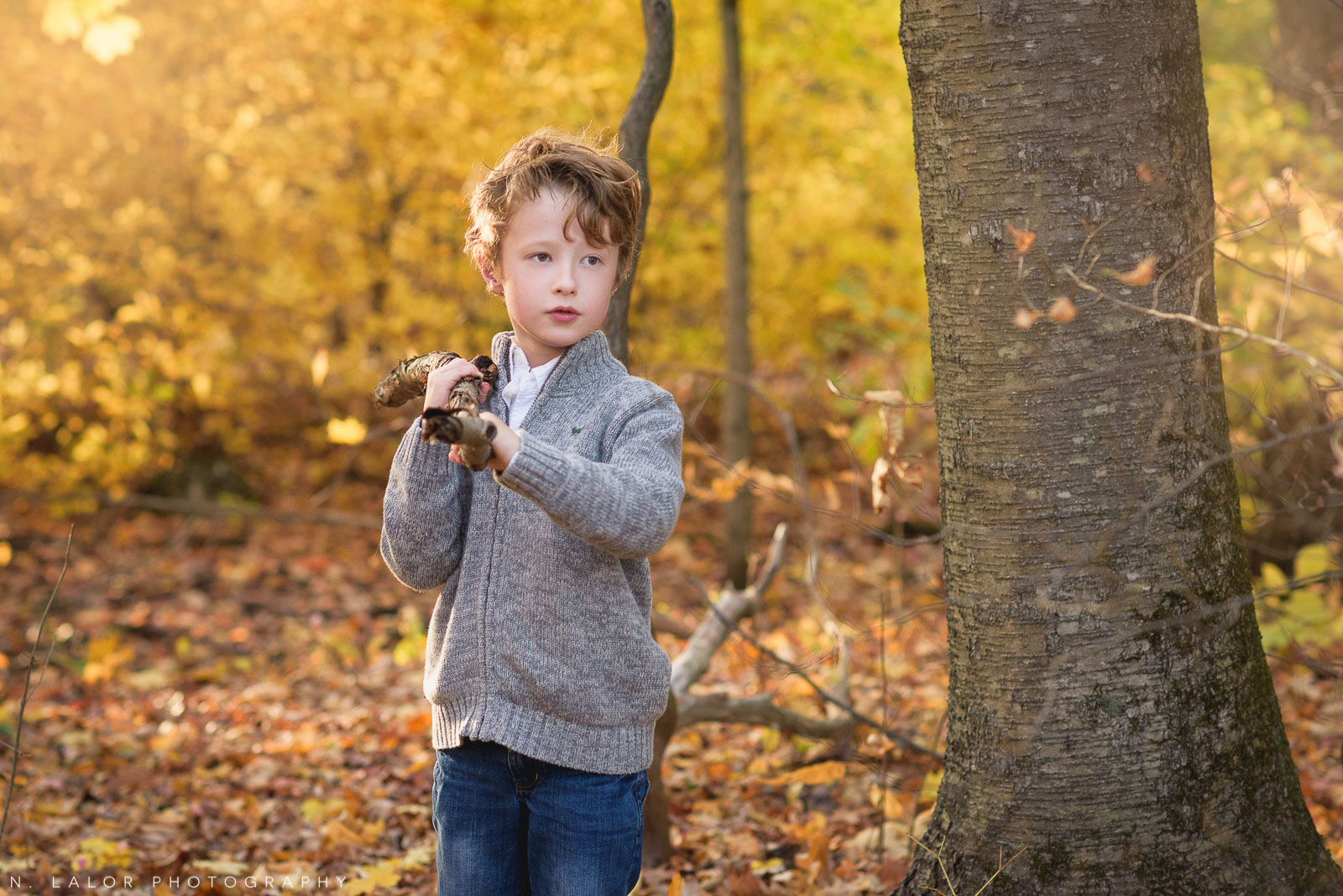 Playing with sticks. A lifestyle portrait of a 6-year old boy at the New Canaan Nature Center. Photo by N. Lalor Photography