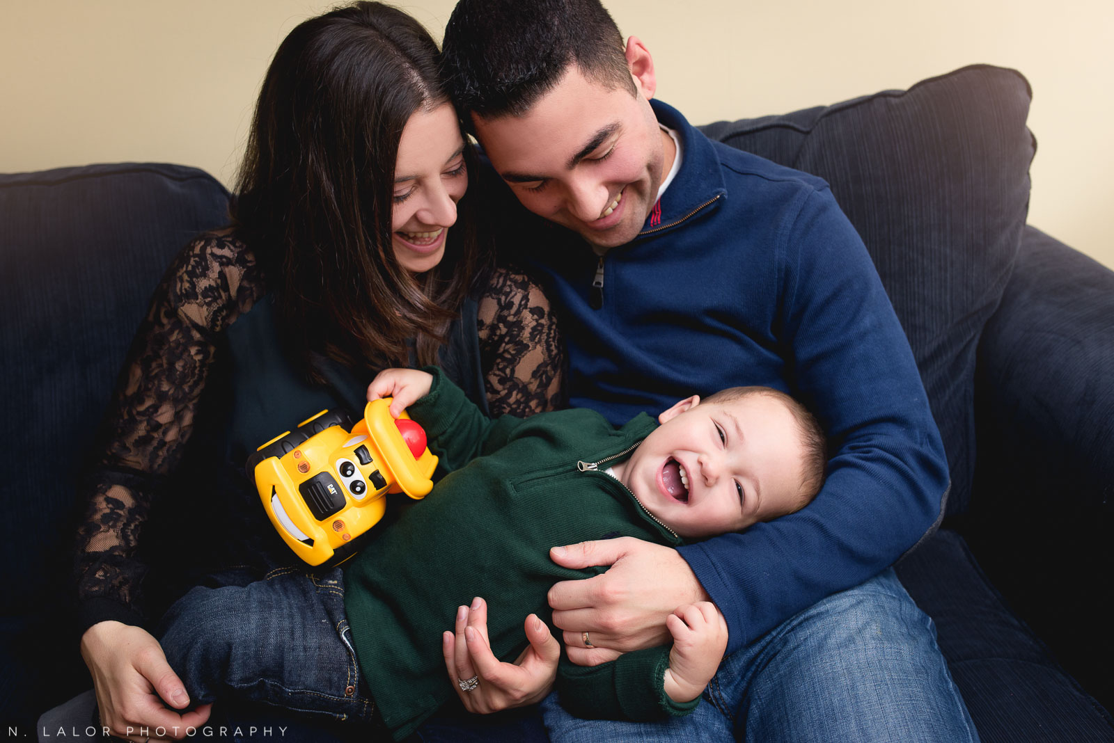 Laughing together.. mom, dad, and their toddler son. Candid lifestyle family portrait by N. Lalor Photography.