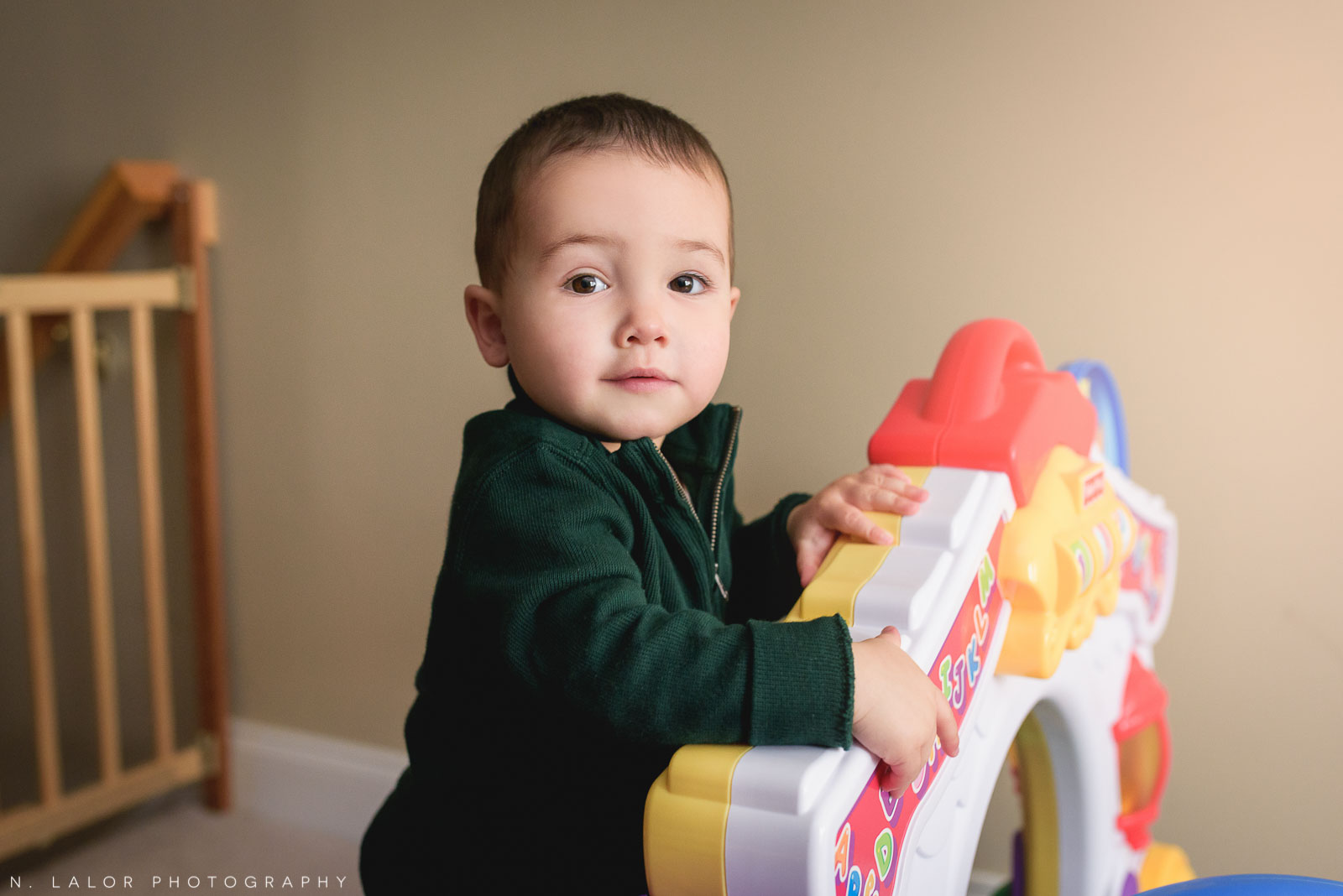 Toddler boy playing with a toy. Lifestyle portrait by N. Lalor Photography.